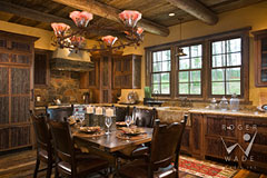 colorful kitchen and dining room of small luxury log home with rustic custom cabinets by The Old World Cabinet Company