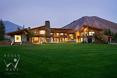 rear elevation of luxury contemporary mountain home at twilight