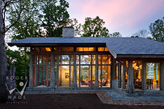 treehouse timber frame home looking through glass walls to living room at twilight