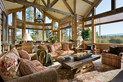 luxury great room of rustic mountain home with reclaimed log walls and timber beams towards windows and Wyoming views