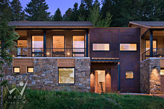 front entry of stone and steel contemporary luxury mountain home at twilight