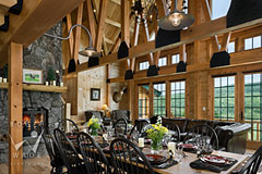 dining room of milled log home with trusses towards fireplace living room and windows
