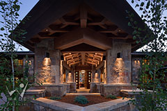porte-cochre towards entry of luxury mountain stone and timber frame lodge