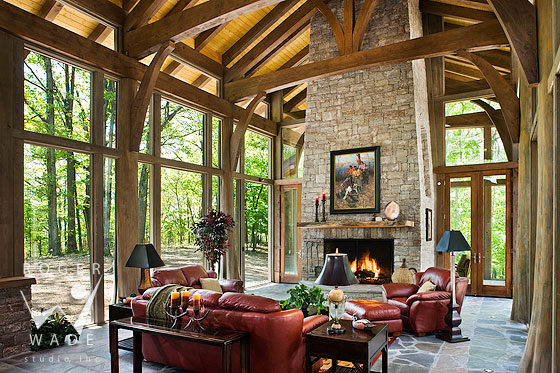 luxury treehouse living room of timberframe home with glass walls and whole tree trunk posts