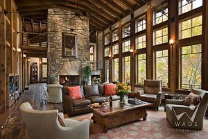 living room of luxury mountain timber frame towards fireplace and wall of windows looking out to fall colors