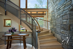 vignette of contemporary curved stairway with wire mesh and wood railing