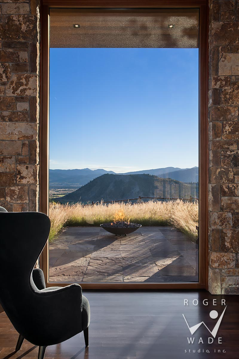 contemporary architectural stock photography, looking out window toward patio with fire pit and mountain view, jackson, wy