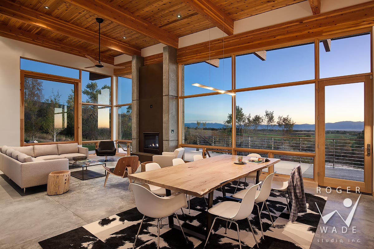 photo of contemporary interior design, living room looking out windows to mountain view at twilight, alta, wy