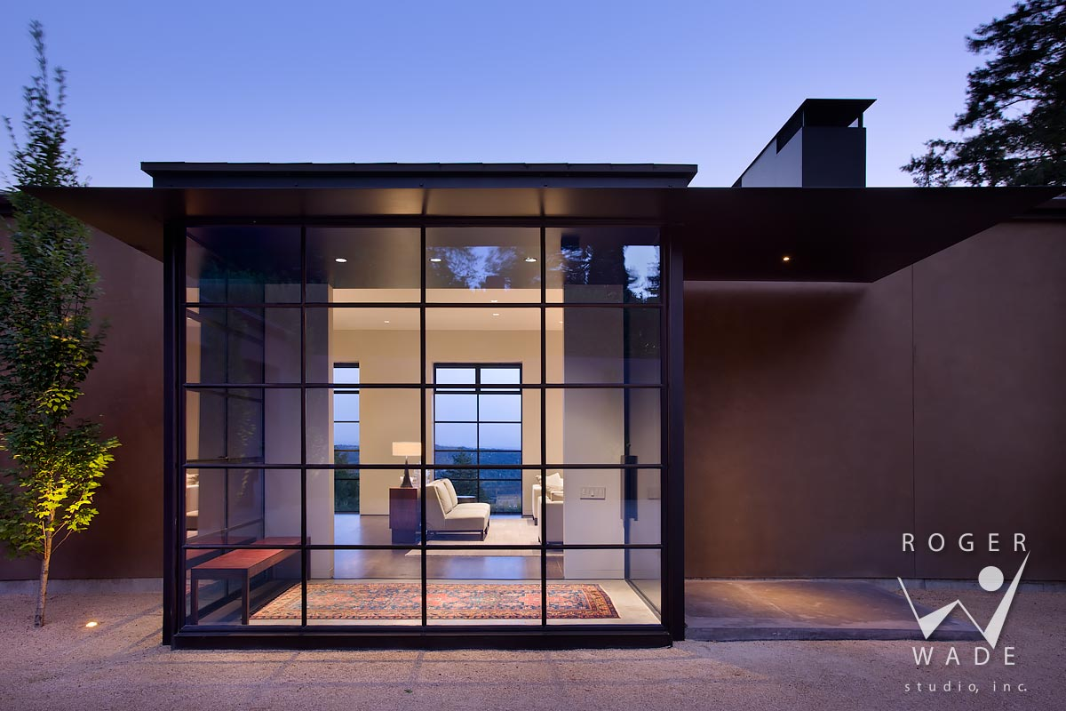 modern architectural photography, front entry of steel and glass, looking into living room at twilight, portland, or