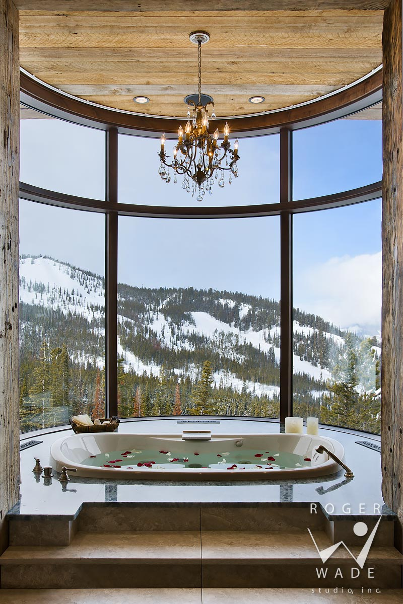 mountain modern interior design, master bathroom tub, looking out curved window to winter scenery and ski resort, big sky, montana