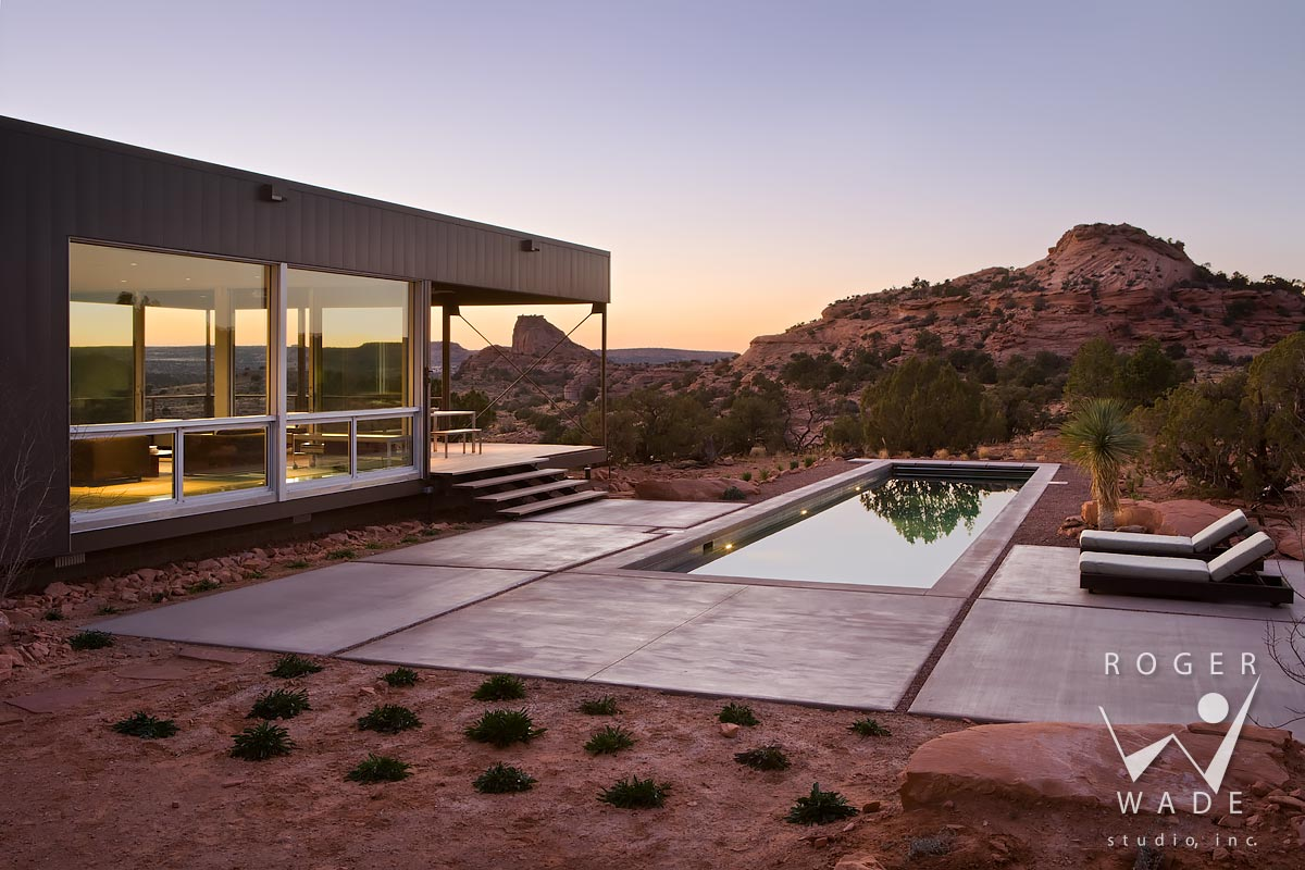 photo of contemporary modular architecture, looking over pool area toward living area wing at twilight, moab, ut