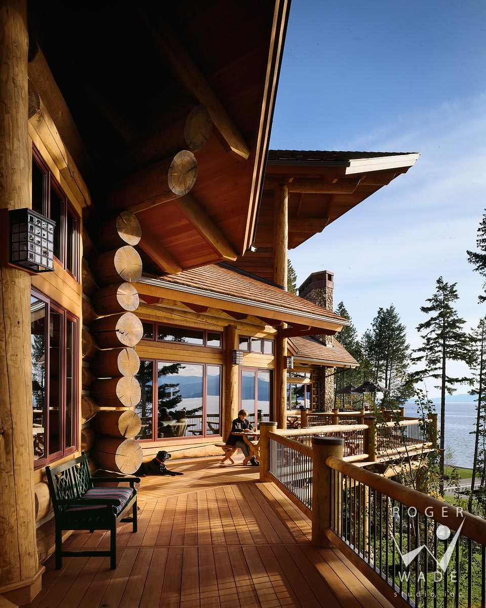 log home, deck detail with woman and dog, looking out to view of flathead lake, woods bay, mt