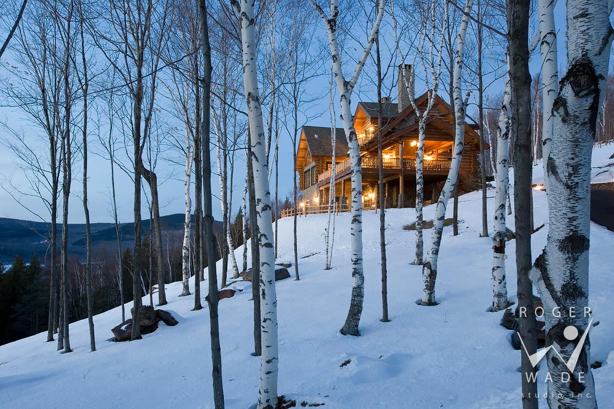 log home photography, winter twilight view of cabin through aspen trees, windham, ny