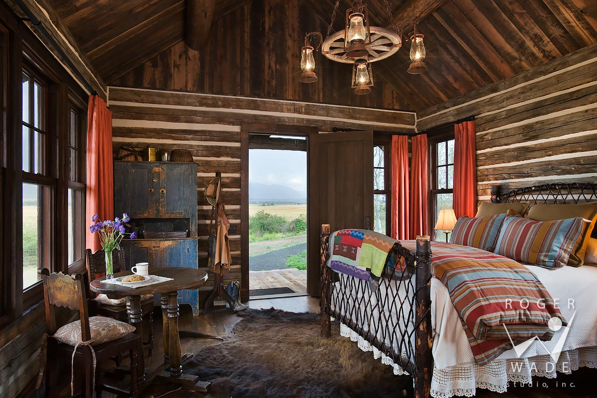 log cabin photography restored cabin toward bed looking out door to ranch view - Log Homes Interior Designs
