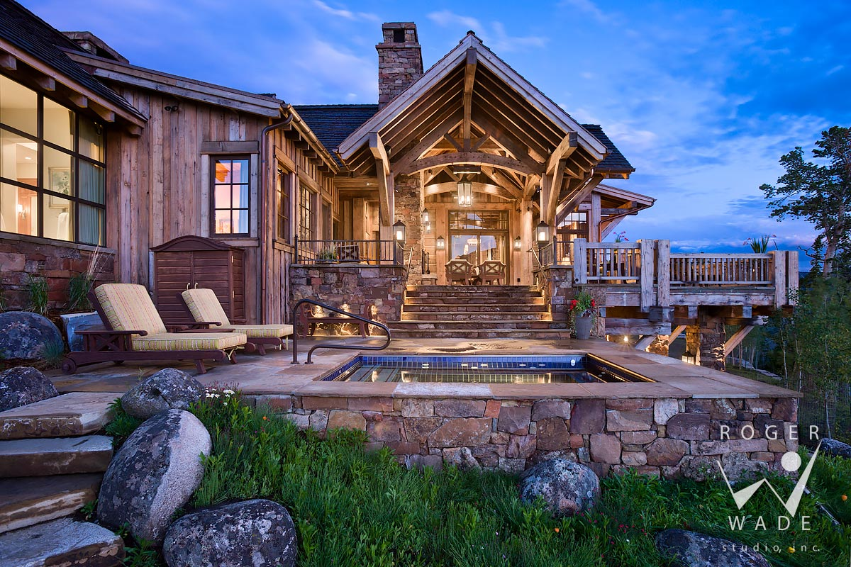 roger wade studio architectural photography of hot tub, patio and rustic covered deck at twilight, luxury mountain timber frame home, yellowstone club, montana, by locati architects, design associates and schlauch bottcher construction
