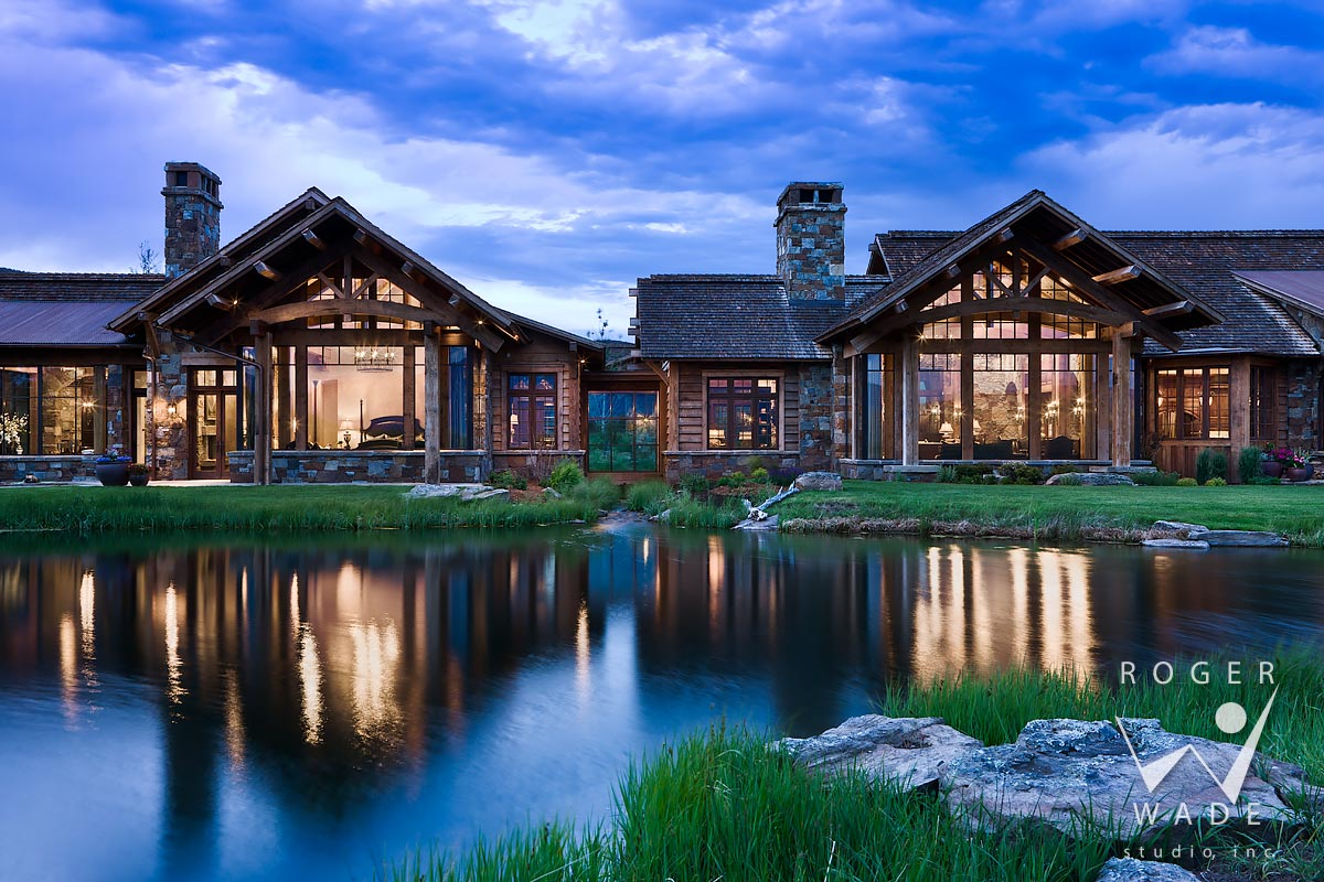 looking over pond toward great room and master suite at twilight, livingston, mt