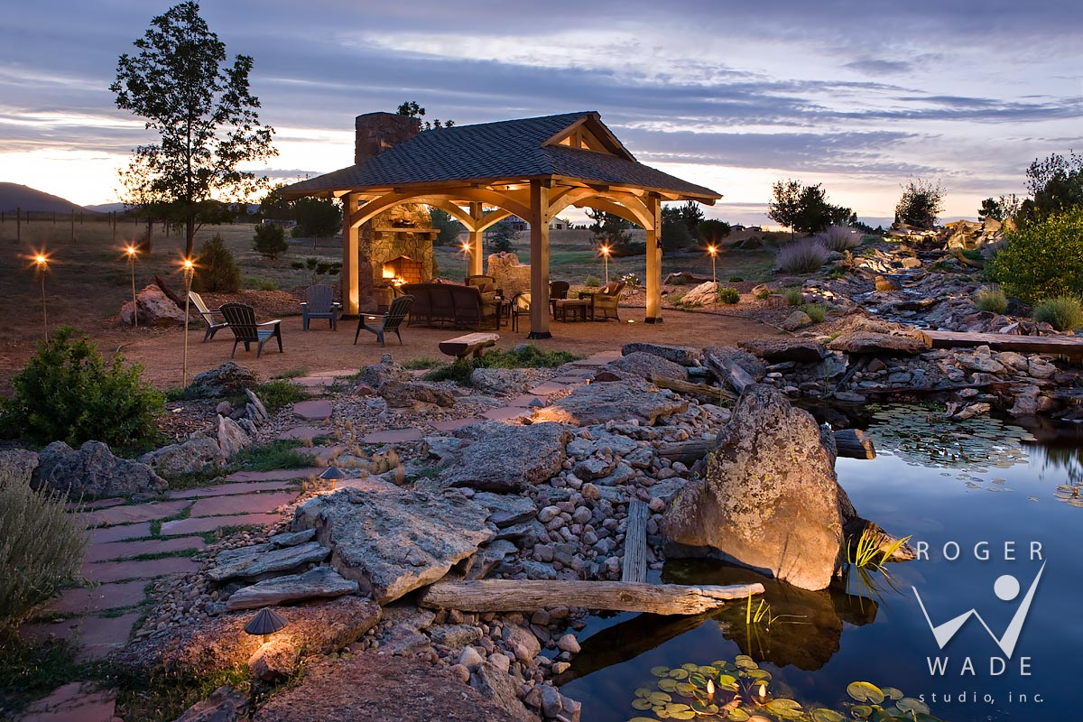timber frame gazebo with fireplace by pond at twilight, loveland, co