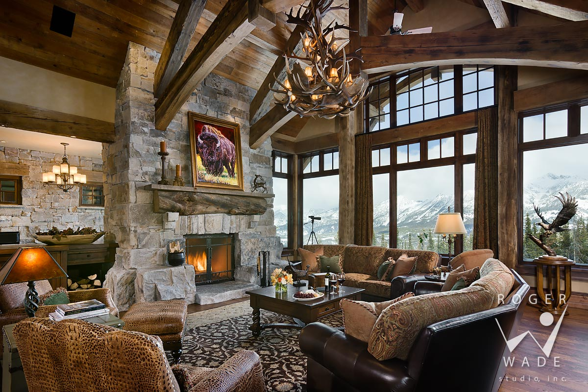 living room toward fireplace and windows looking out to mountain view, big sky, mt