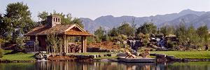 rustic timber pavillion next to landscaped pond and waterfall