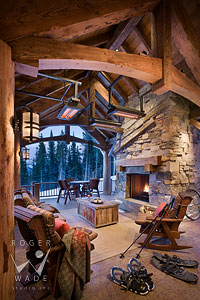 rustic timber covered patio with stone fireplace of luxury mountain home during winter